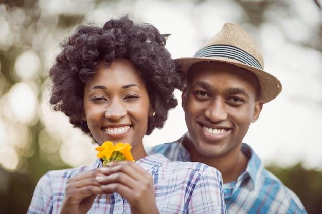 Pareja sonriente sosteniendo flores amarillas en el jardín