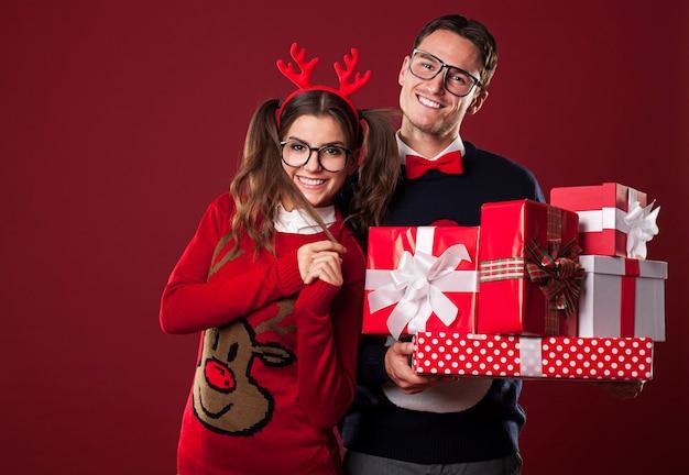 Pareja sonriente sosteniendo la pila de regalos de navidad