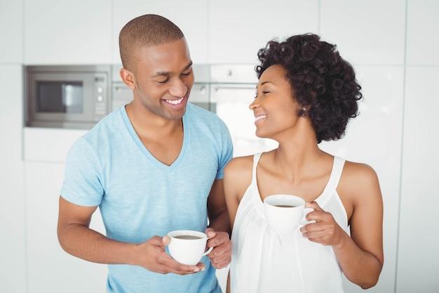 Pareja sonriente sosteniendo tazas en la cocina