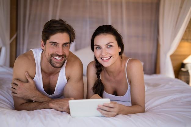 Pareja sonriente con tableta digital en cama en cabaña