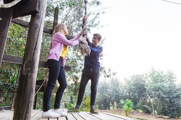 Pareja sonriente tirando de una cuerda en el parque de aventura