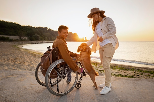 Pareja sonriente de tiro completo con perro en la playa