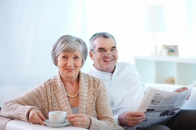 Pareja sonriente tomando café y leyendo el periódico