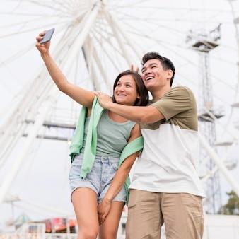 Pareja sonriente tomando selfie juntos