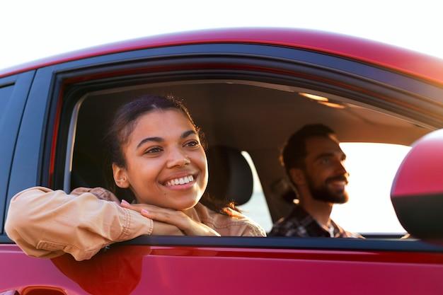 Pareja sonriente viajando en coche