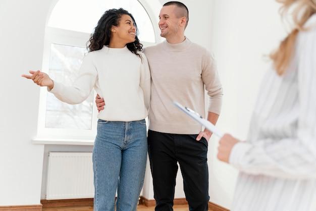 Pareja sonriente viendo nueva casa con agente inmobiliario femenino