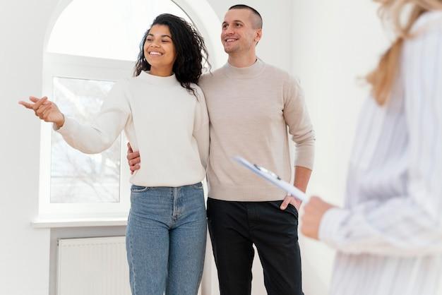 Pareja sonriente viendo nueva casa con agente inmobiliario