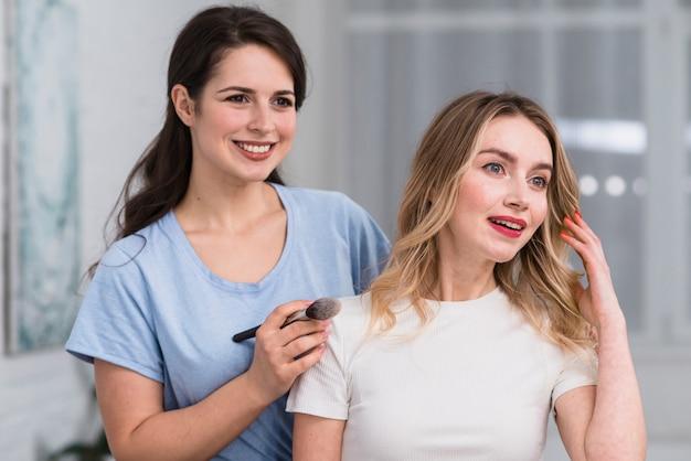 Pareja de sonrientes mujeres hermosas en proceso de maquillaje.