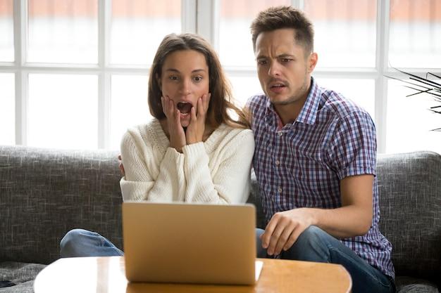 Pareja sorprendida confundida y asustada viendo una película de terror en una computadora portátil