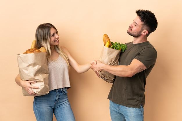 Pareja sosteniendo bolsas de la compra de comestibles