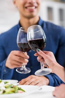 Pareja sosteniendo copas de vino tinto en el día de san valentín