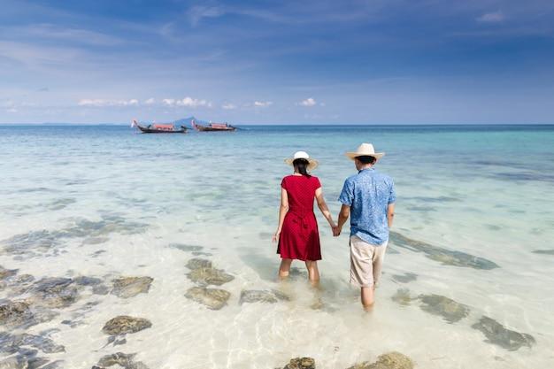 Pareja sosteniendo la mano caminando hacia el mar de aguas cristalinas con un barco de cola larga