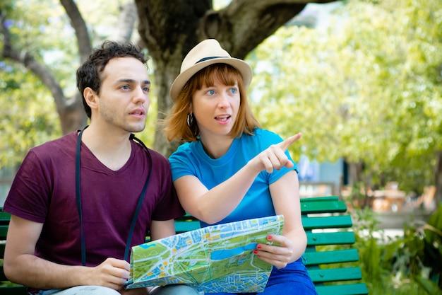 Pareja sosteniendo el mapa en las manos y buscando ubicación