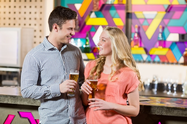 Pareja sosteniendo un vaso de cerveza en el bar