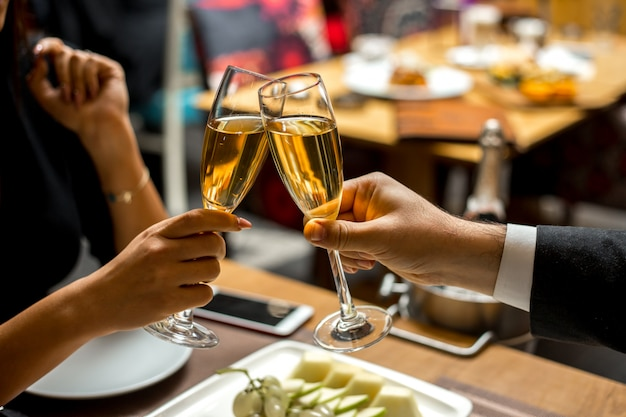 Pareja sostiene las copas con champán con vista lateral de plato de fruta