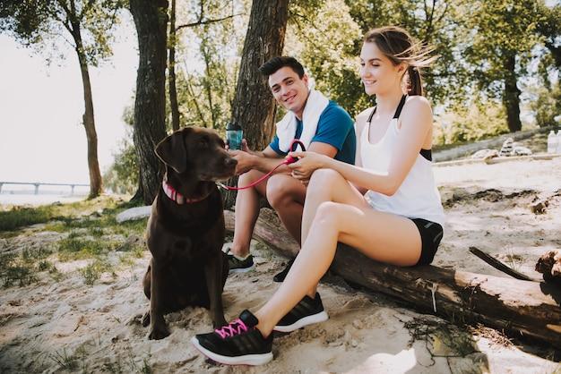 Pareja con su perro hermoso en la orilla del río en green park