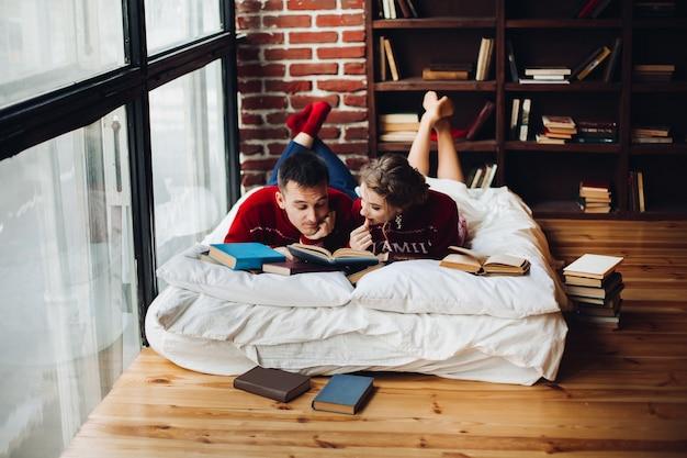 Pareja en suéteres rojos de navidad leyendo libros sobre colchones en casa