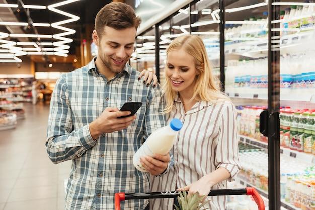 Pareja en supermercado leyendo la lista de compras