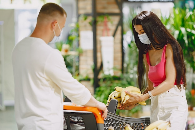 Pareja en un supermercado. señora con una máscara médica. la gente hace parchases.