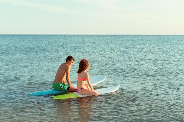 Pareja de surf apoyándose en tablas de surf en el mar
