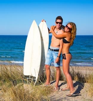 Pareja de surfistas adolescentes abrazan en la playa