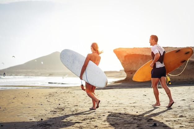 Pareja de surfistas corriendo juntos con tablas de surf en la playa al atardecer - amigos deportivos divirtiéndose yendo a surfear - viajes, vacaciones, concepto de estilo de vida deportivo
