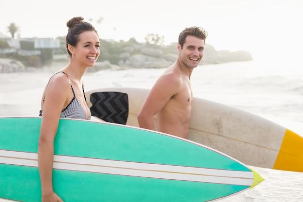 Pareja con tabla de surf en la playa