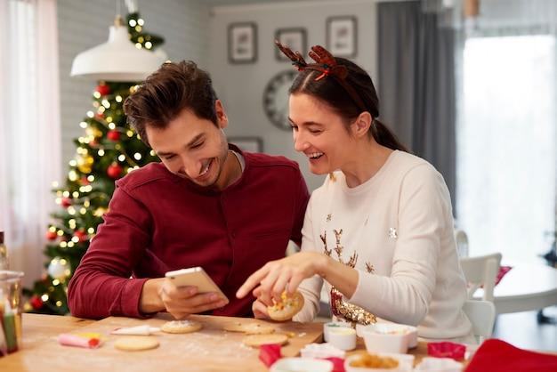 Pareja con teléfono móvil decorando galletas de navidad