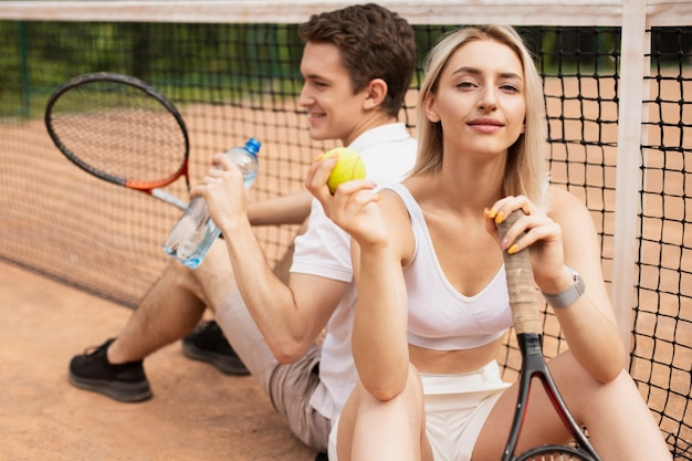 Pareja de tenis activo tomando un descanso
