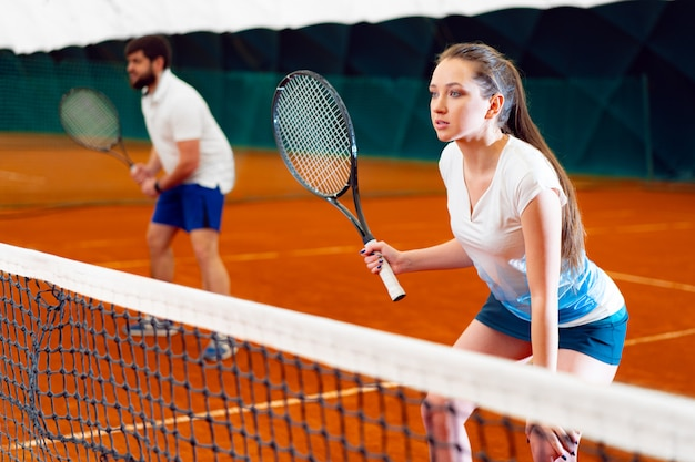 Pareja de tenistas, hombre y mujer esperando el servicio en la cancha cubierta