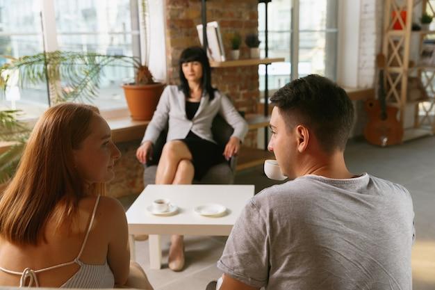 Pareja en terapia o consejería matrimonial. psicólogo, consejero, terapeuta o consultor de relaciones dando consejos. hombre y mujer sentados en una sesión de psicoterapia. familia, concepto de salud mental.