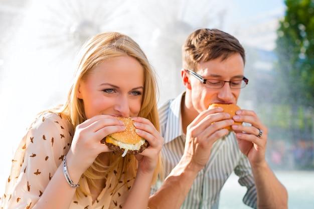 Pareja tiene hambre y come una hamburguesa en el descanso