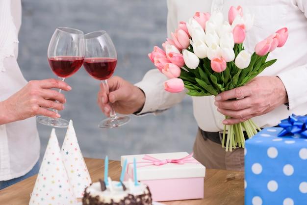 Pareja tintineo de copas de vino con ramo de flores de tulipán; pastel de cumpleaños y cajas de regalo en mesa