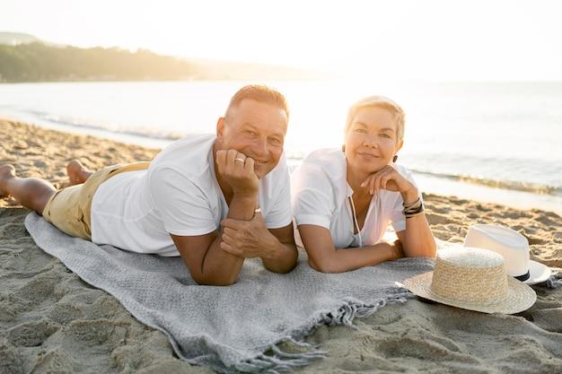 Pareja de tiro completo recostada sobre una toalla en la playa
