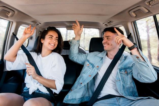 Pareja de tiro medio bailando dentro del coche