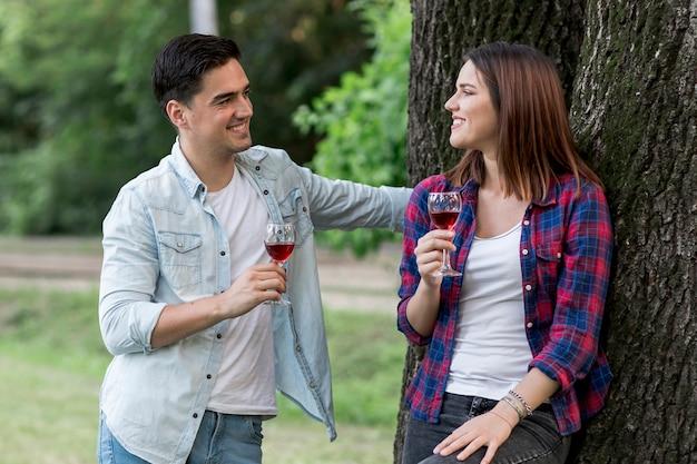 Pareja de tiro medio bebiendo vino tinto en el parque