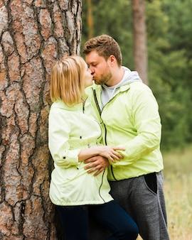 Pareja de tiro medio besándose junto a un árbol