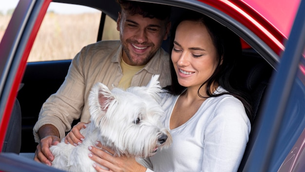 Pareja de tiro medio en coche con perro