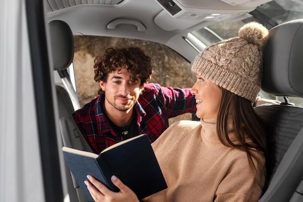 Pareja de tiro medio con libro en coche