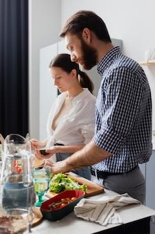 Pareja de tiro medio preparando comida en casa