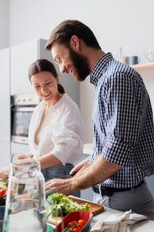 Pareja de tiro medio preparando comida juntos