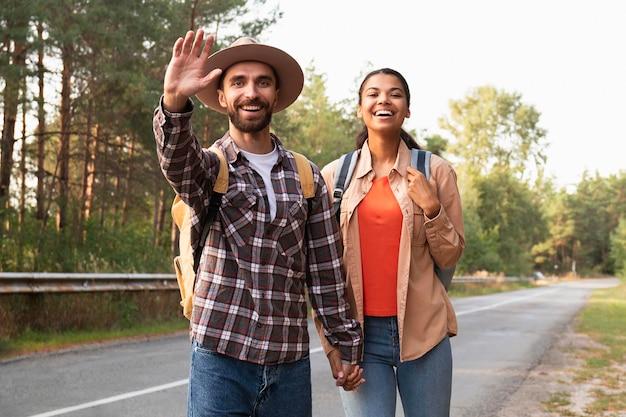 Pareja de tiro medio saludando a alguien mientras viaja