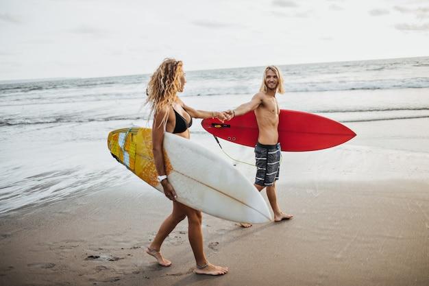 La pareja se toma de la mano y se mira suavemente. hombre y mujer posando con tablas de surf