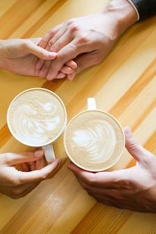 Pareja tomados de la mano en la cafetería tomando café, manos de los amantes. compromiso, el día de san valentín, un chico sosteniendo la mano de su novia. la foto se superpone con arena y ruido.