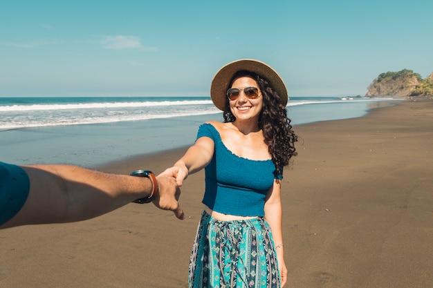 Pareja tomados de la mano caminando en la playa