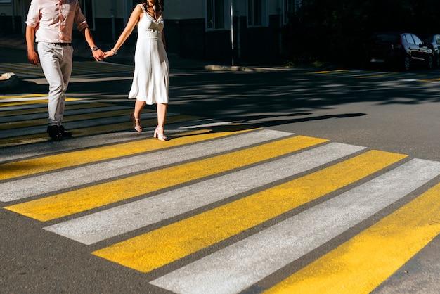 Pareja tomados de la mano cruzando la intersección de la ciudad
