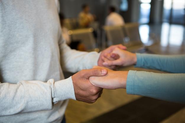 Pareja tomados de la mano en la sala de espera en la terminal del aeropuerto