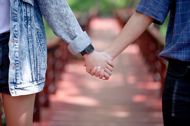 La pareja tomados de las manos muestra amor en el día del amor.