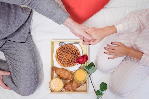 Pareja tomados de las manos sobre la bandeja con el desayuno