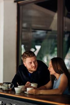 Pareja tomando café y hablando en la cafetería.